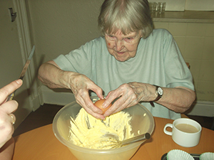 Woman cracking an egg on Carrot Cake Day