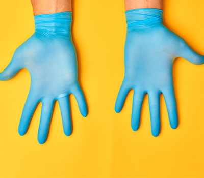 infection control - hands in plastic gloves
