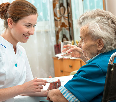 healthcare – a nurse helps an elderly resident with her medication