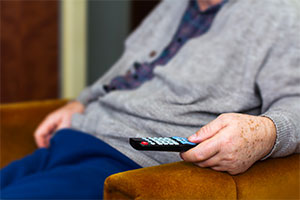 TV licence fee - an elderly man with TV remote in hand