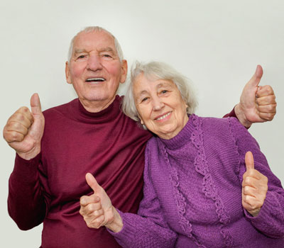 Old couple from Robinson House Care Home giving the thumbs up sign