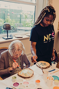 Volunteer from NCS Young People painting with an older lady at Borough Care's Lisburne Court