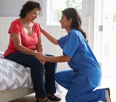 Care home bedroom with elderly lady and care worker - What makes a safe home for the elderly?