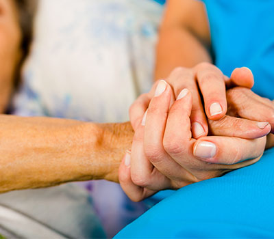 Social care – a nurse holds an elderly patient's hand