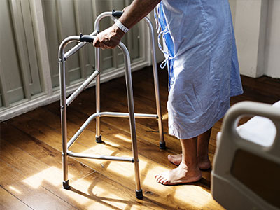 Elderly person walking with aid protected with care home insurance