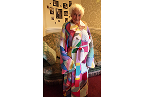 Hazelgrove Court Care Home resident Joyce Baxtrum modelling a dressing gown created by residents as part of a Knit for Peace UK initiative