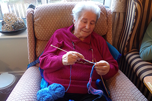 Hazelgrove Court Care Home resident Pat Keleher knitting a belt for a dressing gown as part of a Knit for Peace UK initiative