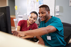 healthcare jobs - two workers look at a screen