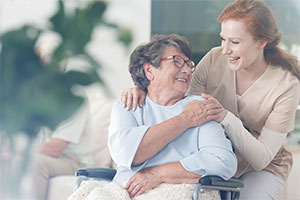 Old lady in wheelchair with carer happy knowing her care home uses an efficient care management solution