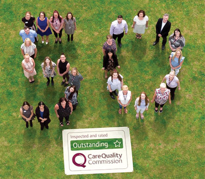 "Home Instead Senior Care staff celebrating receiving their 50th ""outstanding"" CQC rating"