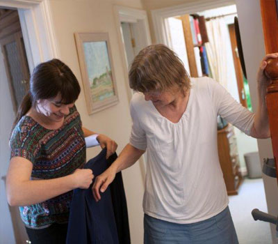 Care home staff helping older people put on their coats so they can go outside and vote