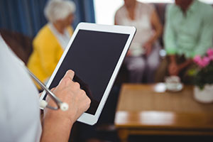 Social care sector urged to back recruitment campaign - nurse on ipad